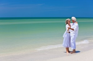 Happy Senior Couple Dancing Holding Hands on Tropical Beach