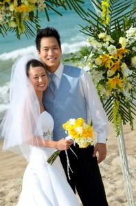 Newlywed Couple Stand on a Beach Under a Pergola